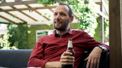 Young, happy man relaxing and drinking beer in cafe in garden  Stock Footage