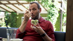 Happy man eating ice cream sitting in cafe in garden Stock Footage