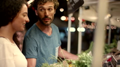 Expat couple buying vegetable at market. - stock footage