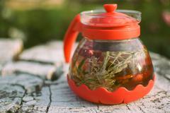 Teapot of fruit tea with herbs and berry on the white tree stump Stock Photos