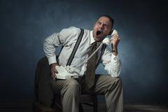 Screaming angry retro 1940 man on the phone sitting on chair in room. Stock Photos