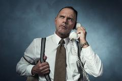 Angry retro 1940 man on the phone sitting on chair in room. Stock Photos