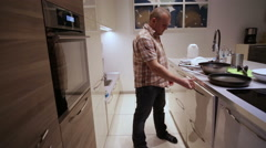 Man Puts a Frying Pans in the Dishwasher Stock Footage