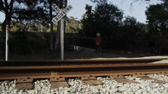 Young attractive woman walking across train tracks 4K stock video footage - stock footage
