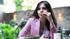 Young, pretty woman eating snack while sitting in cafe in garden Stock Footage