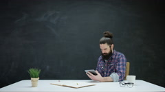 4K Hipster man working on tablet & looking at chalkboard behind for inspiration Stock Footage