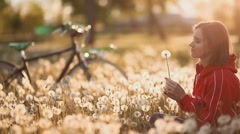 Female sitting and blowing a dandelion. In the park Stock Footage