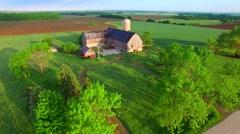 Rustic abandoned farm amid lush, scenic springtime fields - stock footage