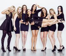 Many diverse women in line, wearing fancy little black dresses, party makeup - stock photo
