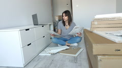 Young woman with instruction trying to match pieces of furniture on floor at hom Stock Footage