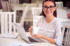 Pleasant woman sitting at the table - stock photo