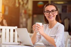 Cheerful woman sitting at the table - stock photo