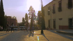 Slow motion of school aged children and families walking in a plaza in Mexico - stock footage