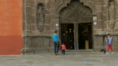 A mother and her young son enter an old church in San Miguel de Allende Stock Footage