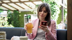 Young woman using smartphone and drinking beverage in cafe in garden Stock Footage