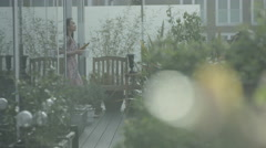 4KYoung woman relaxing with computer tablet in apartment roof garden in the city Stock Footage