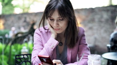 Young woman using smartphone sitting in cafe in garden Stock Footage