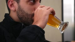 Young man drinking beer - stock footage