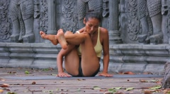 Asian young woman doing hatha yoga in abandoned temple Stock Footage