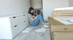 Woman using tablet while matching furniture at her new home Stock Footage