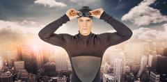 Composite image of swimmer in wetsuit wearing swimming goggles - stock photo