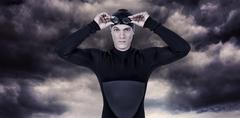 Swimmer in wetsuit wearing swimming goggles against gloomy sky Stock Photos