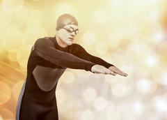 Swimmer in wetsuit while diving against glowing background - stock photo