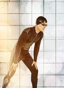 Swimmer in wetsuit and swimming goggles against wall background - stock photo