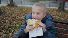 Boy sitting on a bench in the autumn eating Stock Footage