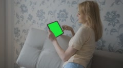 Beautiful girl using tablet with pre-keyed green screen sitting on sofa at home - stock footage