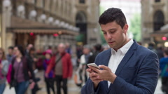 Handsome Young Business Man Using His Cellphone On A Crowded Street Internet - stock footage