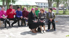 : elderly people sitting on benches outside in summer Stock Footage