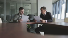 Businessmen in suits and ties discuss a case sitting at a table. Stock Footage