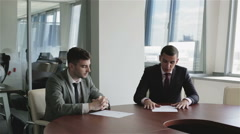 Сo-founders of the business take a counsel at the table. - stock footage