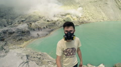 Teenager in gas mask taking selfie photo, video by Ijen volcano in Java, Indones Stock Footage