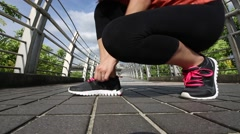 Asian woman running jogger tying shoelace on bridge of urban city a hot day -Dan Stock Footage