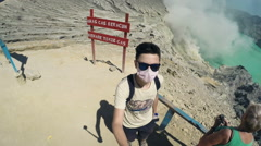 Teenager in dust mask taking selfie photo, video by Ijen volcano in Java, Indone Stock Footage