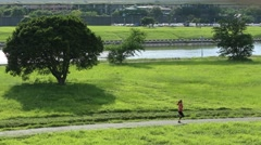 Sports lifestyle. Road runner young asian woman running in beautiful park -Dan - stock footage