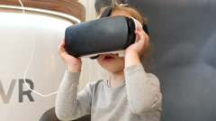 Little child kid girl watching animation film through 3D virtual reality glasses Stock Footage