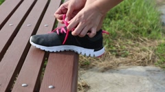 Asian woman running jogger tying shoelace on a bench of park, close up shoe -Dan Stock Footage