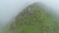 AERIAL, Mountain climber summit trekking foggy mountain peak Stock Footage