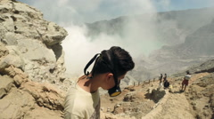 Teenager in gas mask walking down Ijen volcano crater in Java, Indonesia Stock Footage