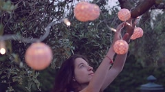 slow motion shot of young woman playing with lantern in the garden - stock footage