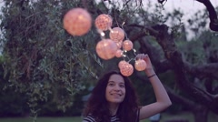 Slow motion shot of young woman playing with lantern in the garden Stock Footage