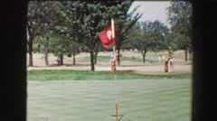 1968: Left handed man hitting golf ball from sand trap onto green near pin hole. - stock footage