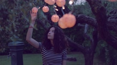 young woman playing with lantern in the garden - stock footage