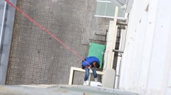 Industrial climber climbing down rope in corner of apartment building Stock Footage
