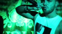 Brutal guy rapping into microphone and gesturing at club scene Stock Footage