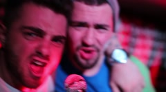 Two boys holding each other to singing along microphone and dancing Stock Footage