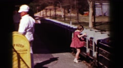 1957: Mini locomotive railroad train takes young girl and mom around park. Stock Footage